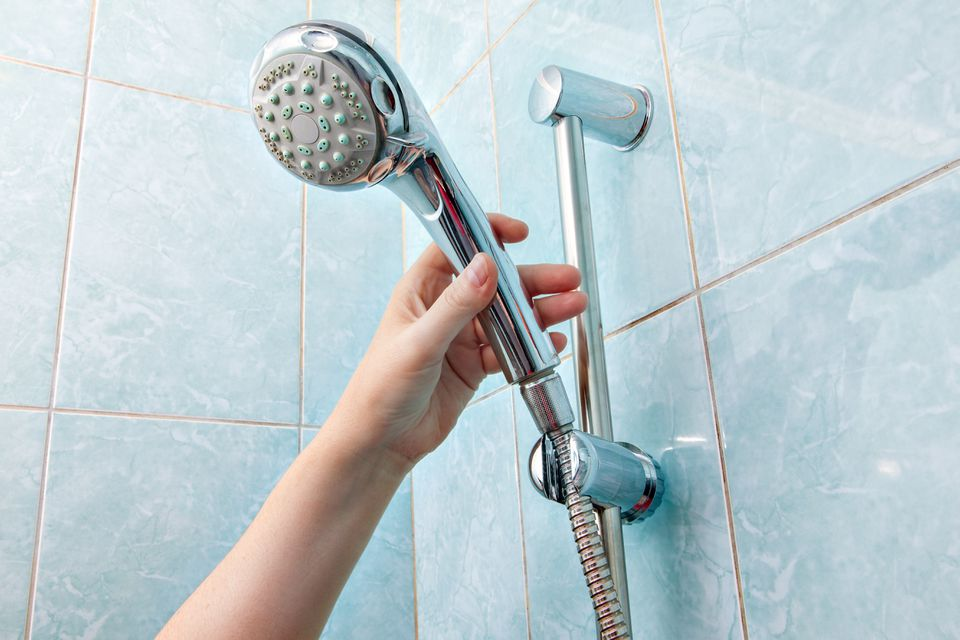 Close-up of human hand adjusts holder shower head with hose