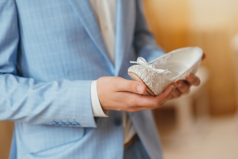 Groom in a blue dress holding wedding shoe bride