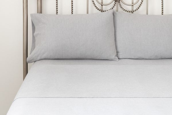 Gray bed sheets neatly dressed on bed