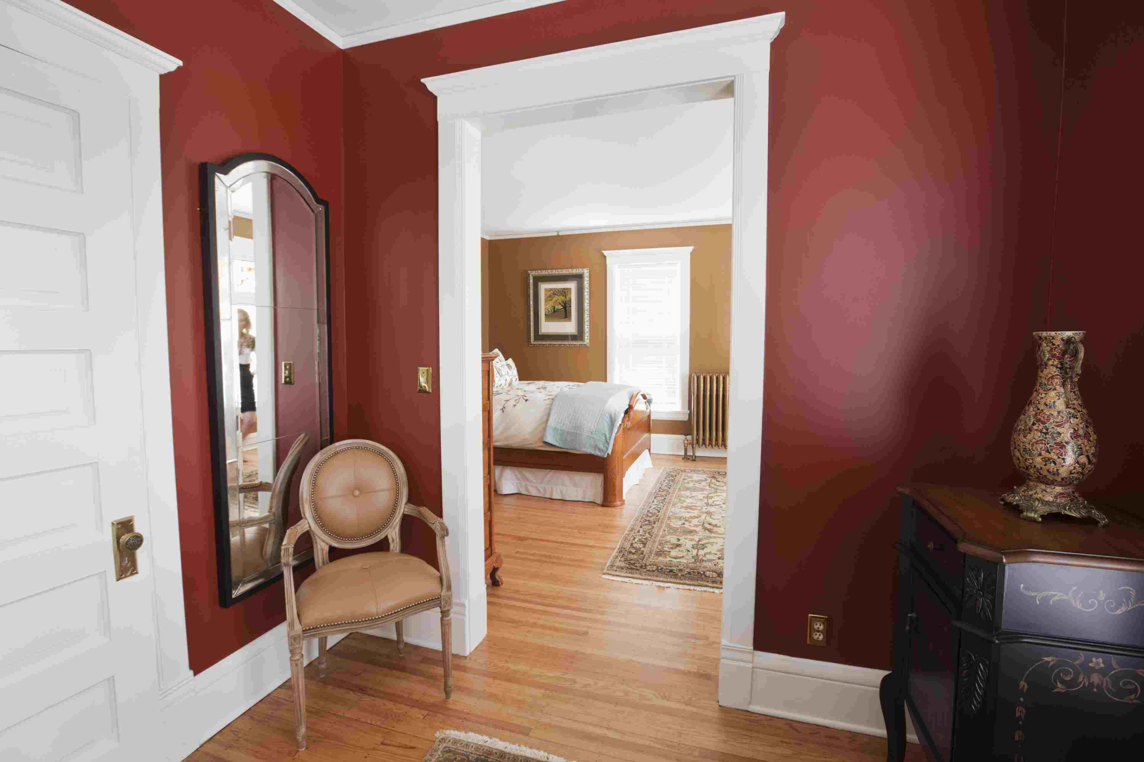 Open doorway leads from smaller room into larger bedroom in Victorian house
