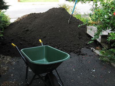 green wheelbarrow in front of pile of dark topsoil in driveway by wooden raised bed