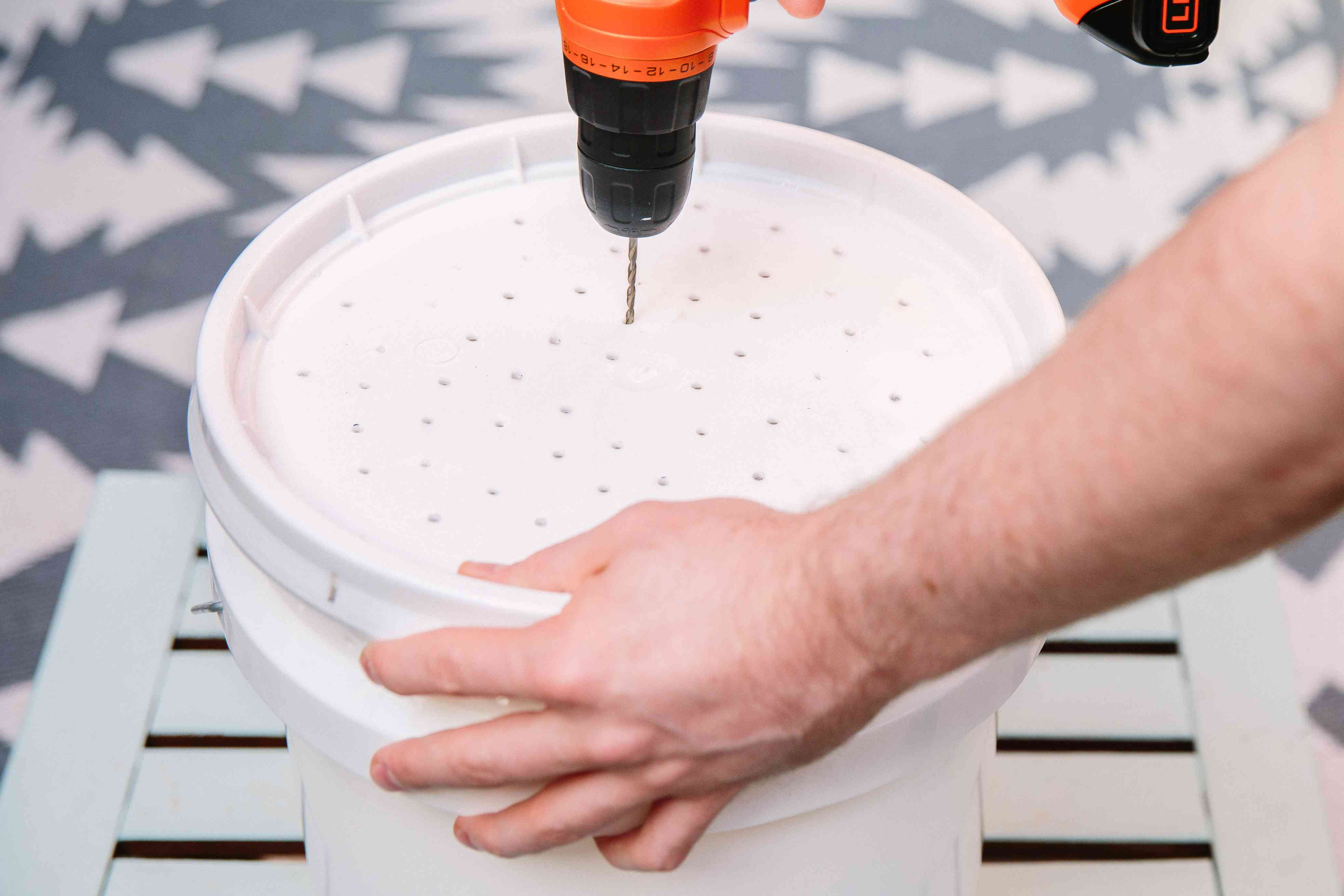 drilling holes in the lid of a bucket