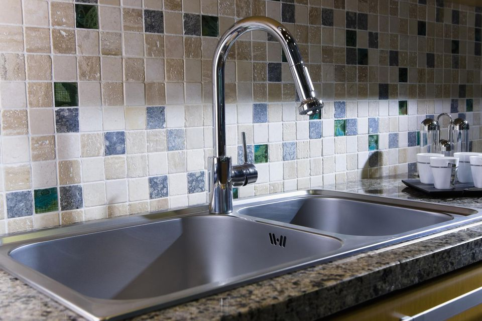 Kitchen sink against tile backsplash.