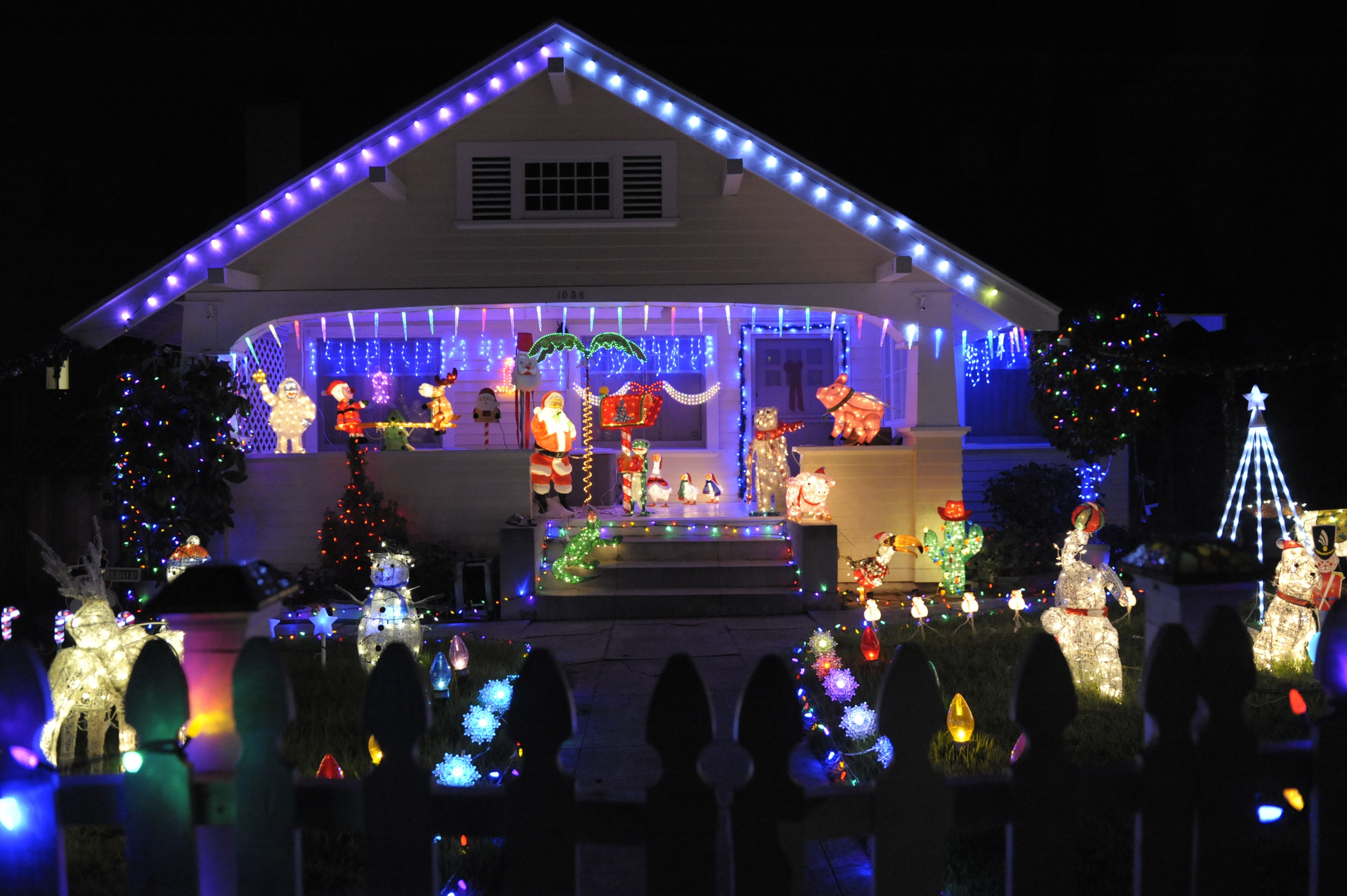 blue lights along the front gable and horizontally above the front porch create a pediment on a modest home