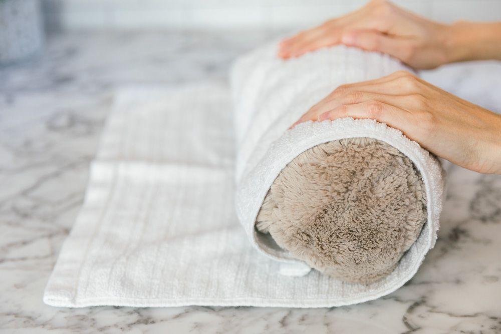 rolling a stuffed animal in a towel