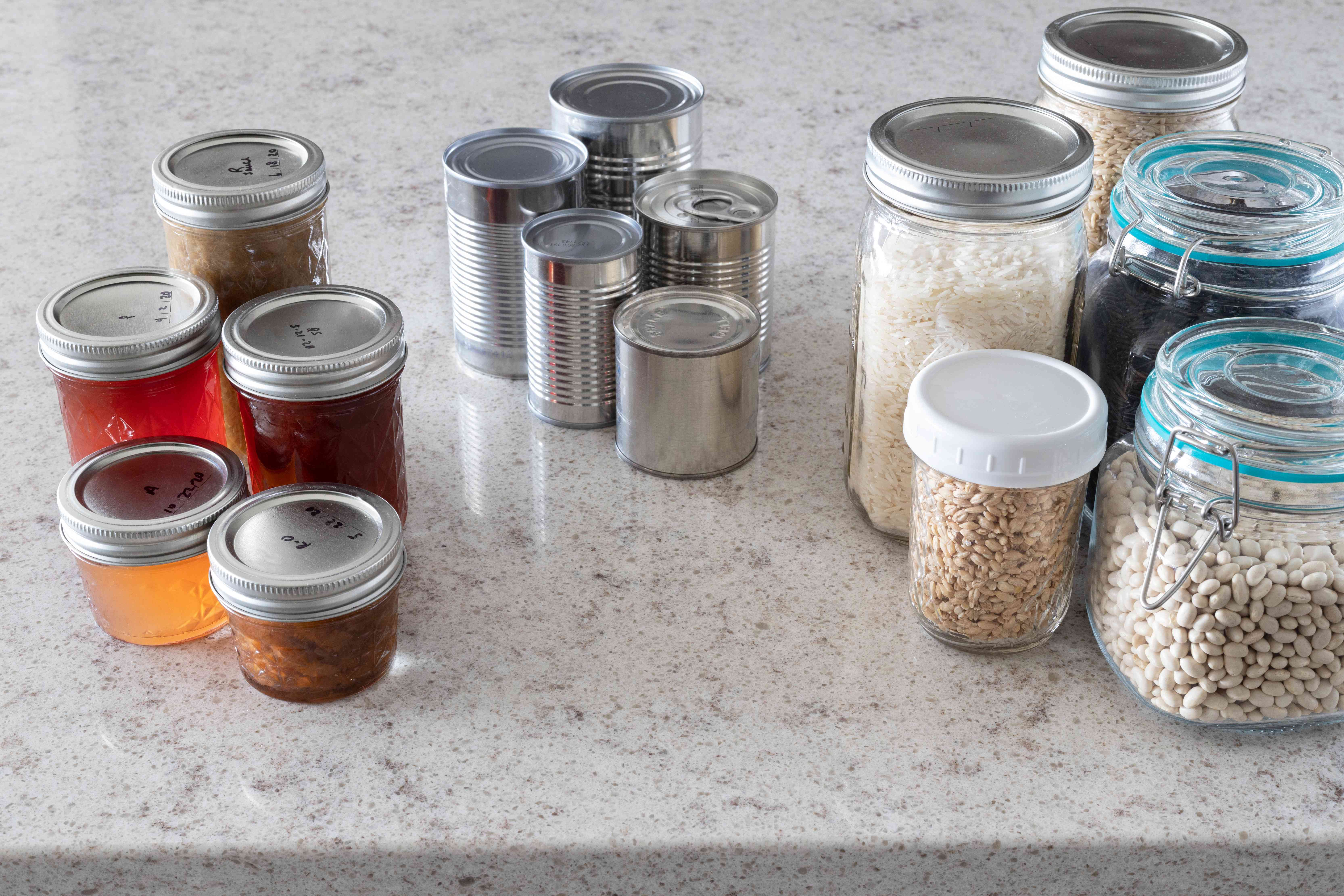 Kitchen pantry items separated into sections on marbled countertop