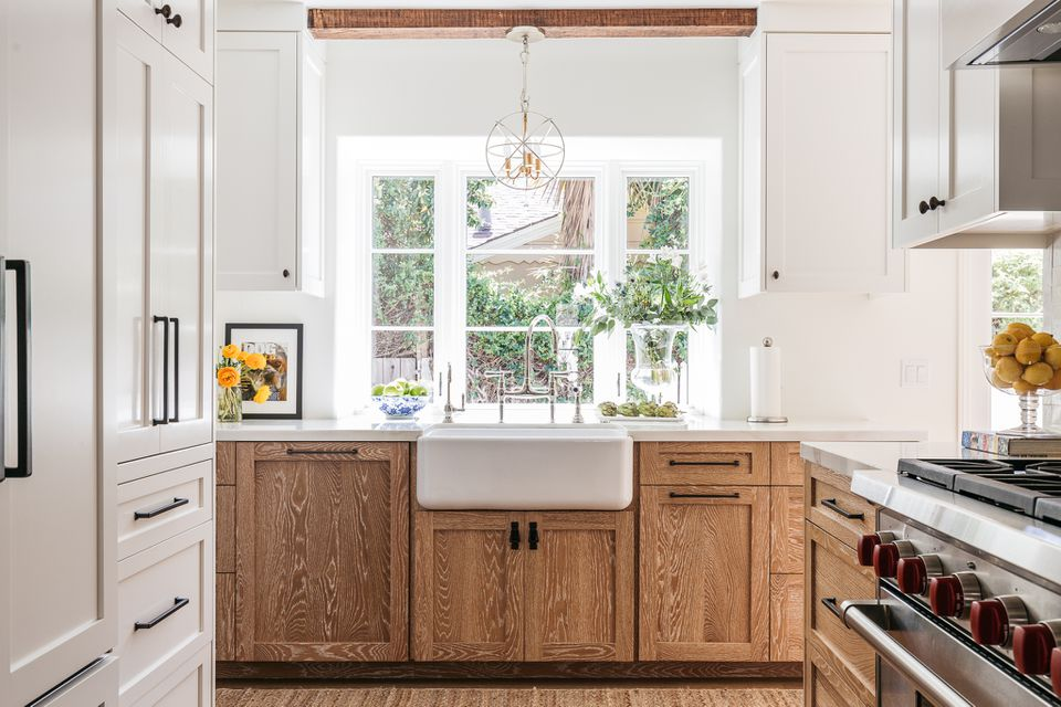 White farmhouse sink surrounded by wooden cabinets and light-filled window above