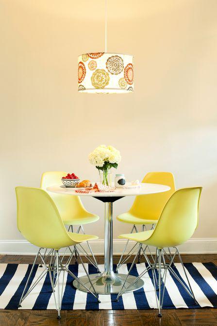 Comedor con sillas amarillas brillantes y una alfombra moderna a rayas