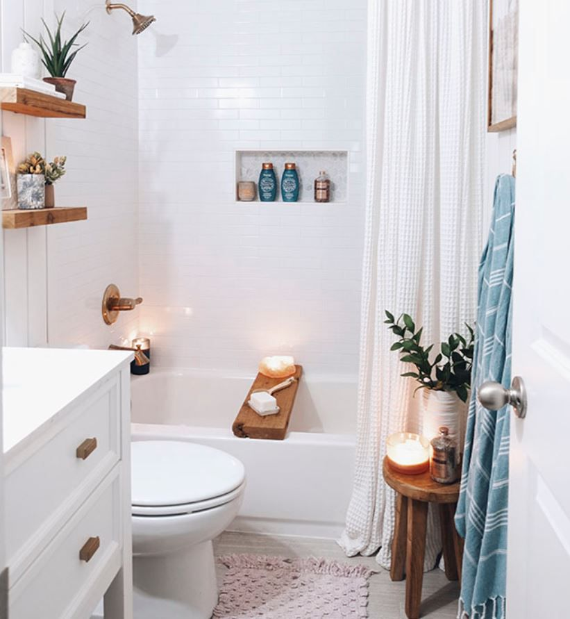 Updated bathroom with subway tile walls, wood details, and lit candles.