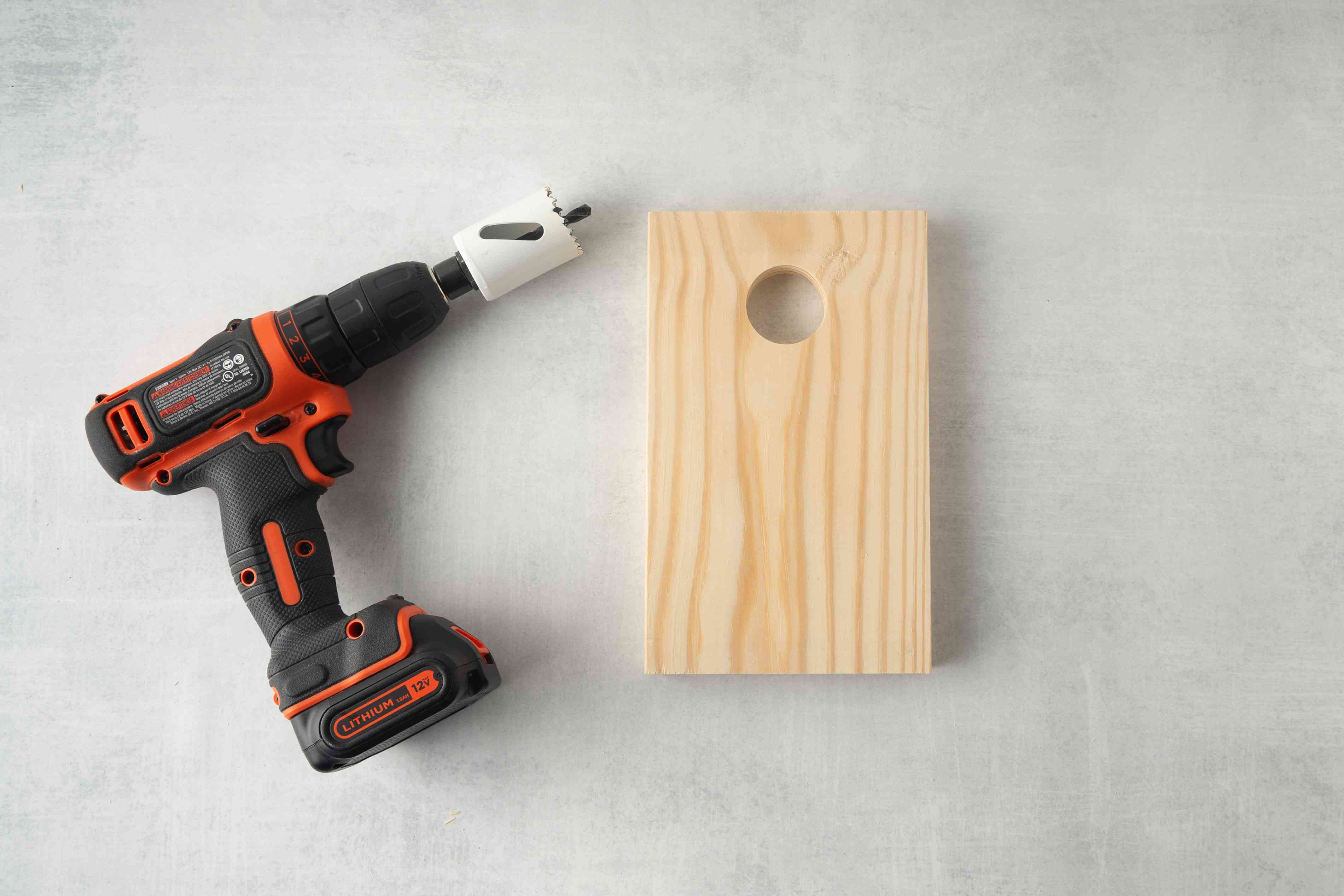 A drill with a hole saw attached next to a pineboard.