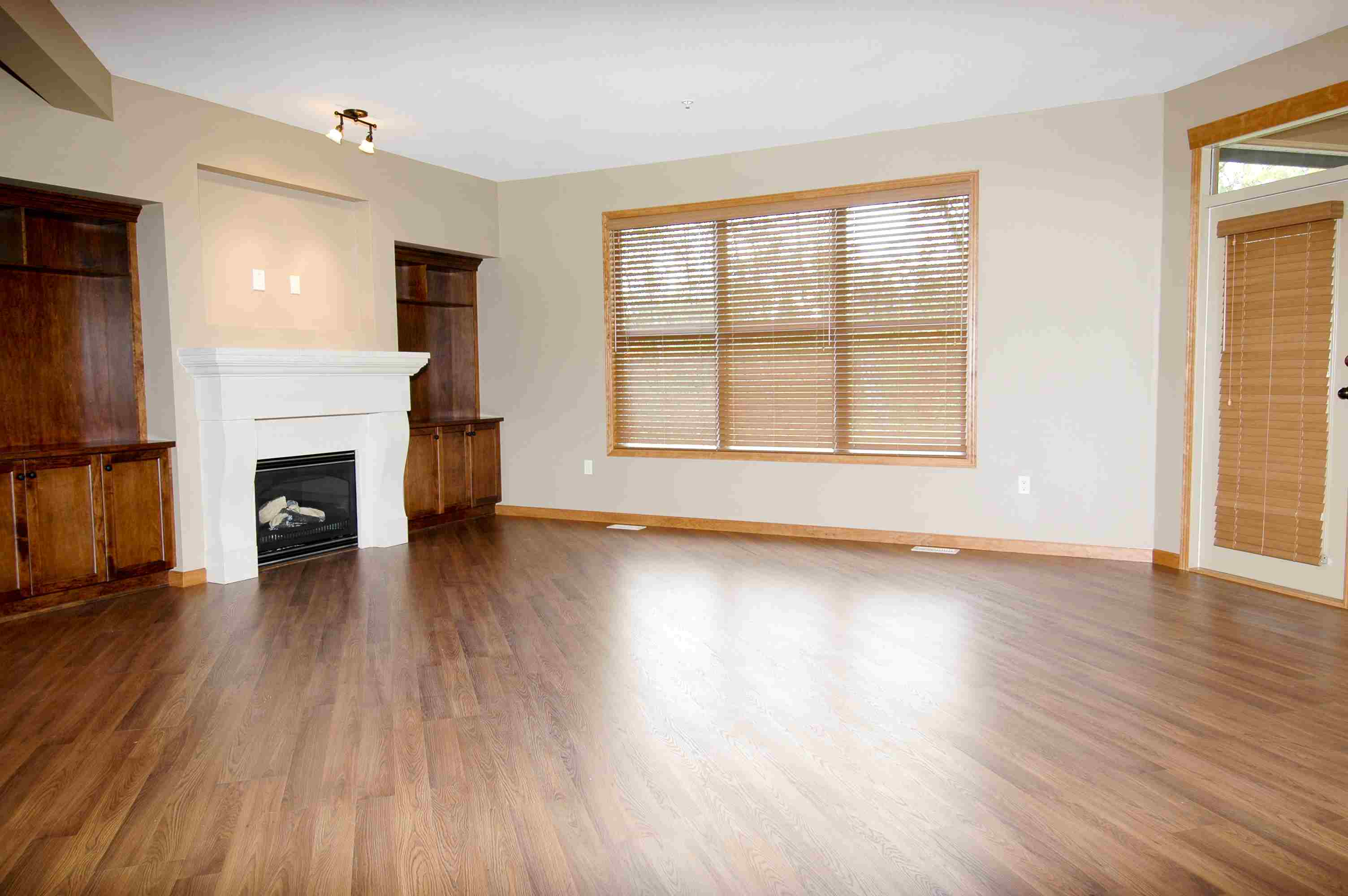 Large empty room with fireplace and wood flooring