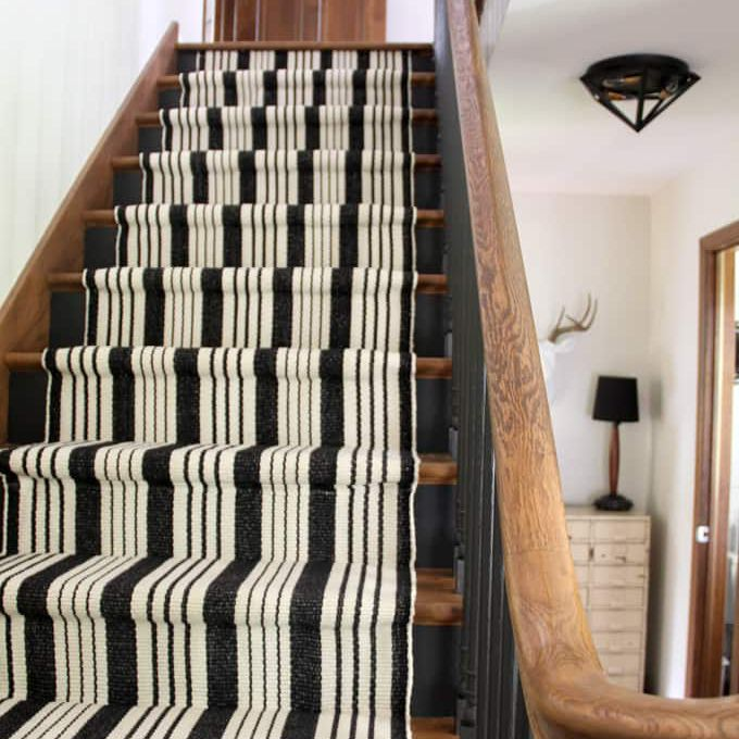 black stairs with a white and black runner