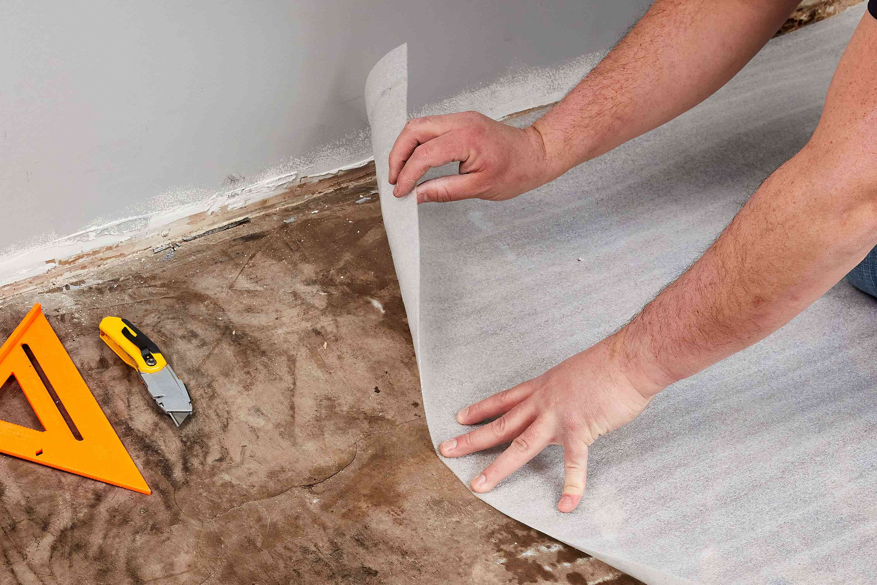 Underlayment being laid out on subfloor