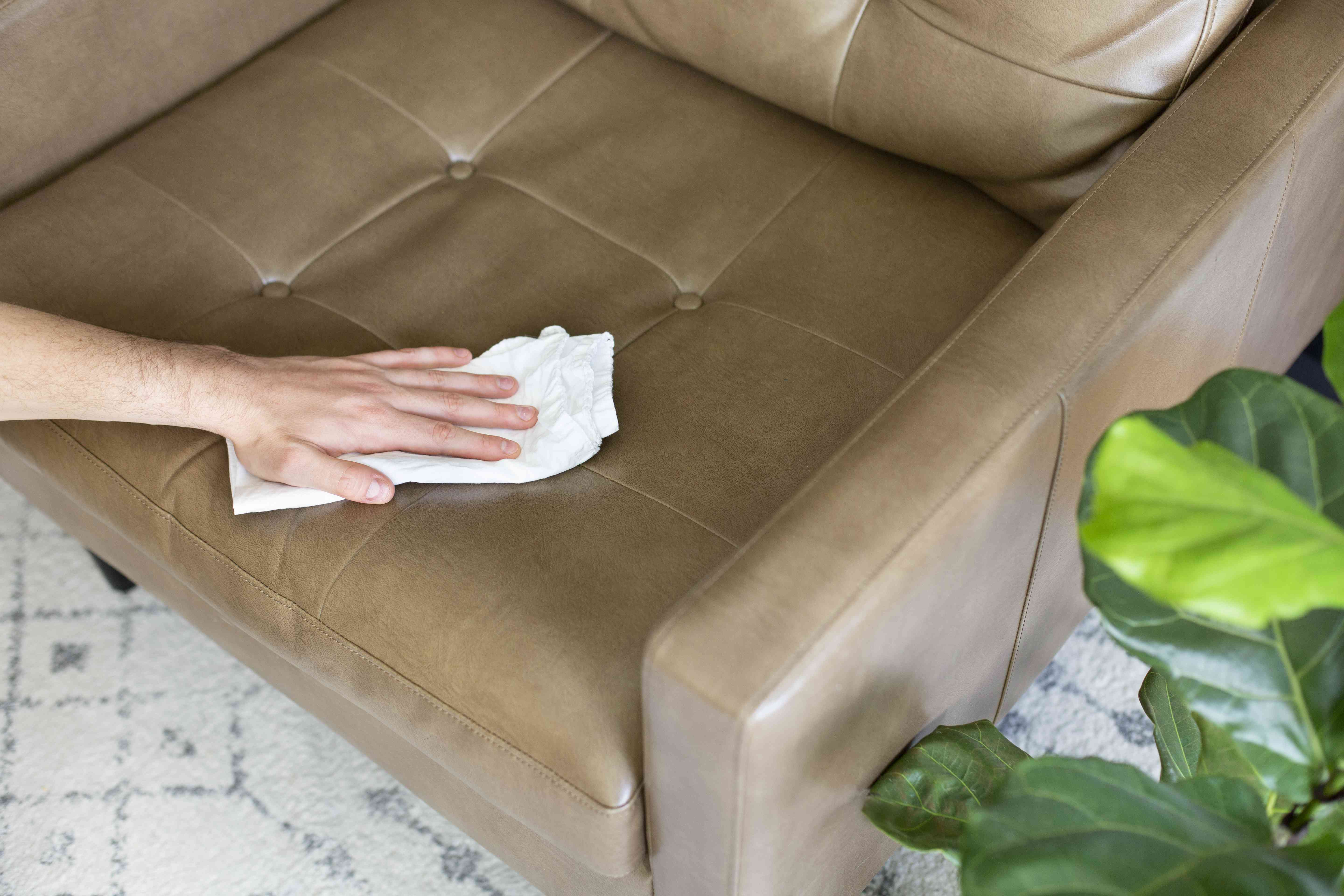 person going over the chair with a dry cloth