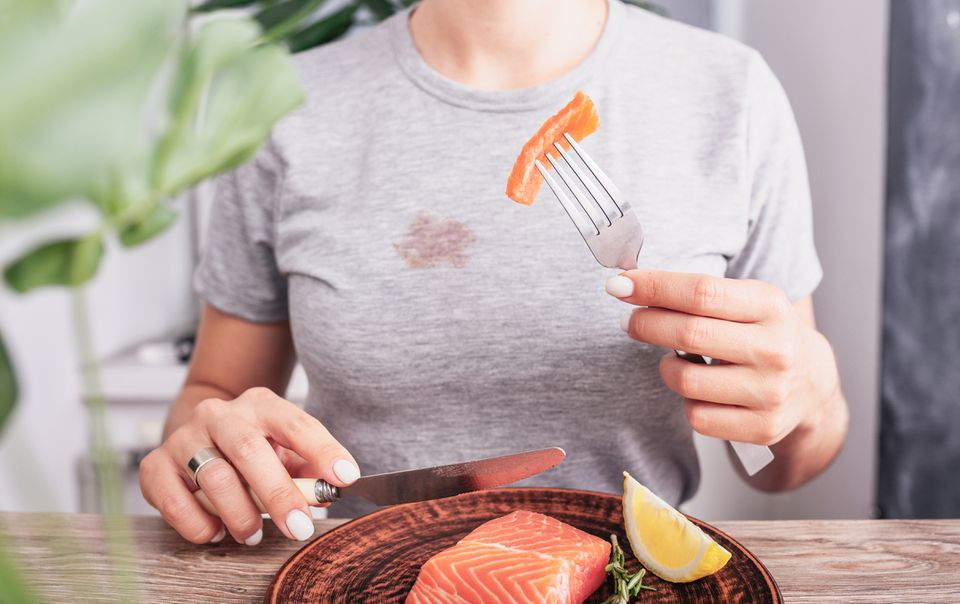 person eating salmon and stain on tee shirt