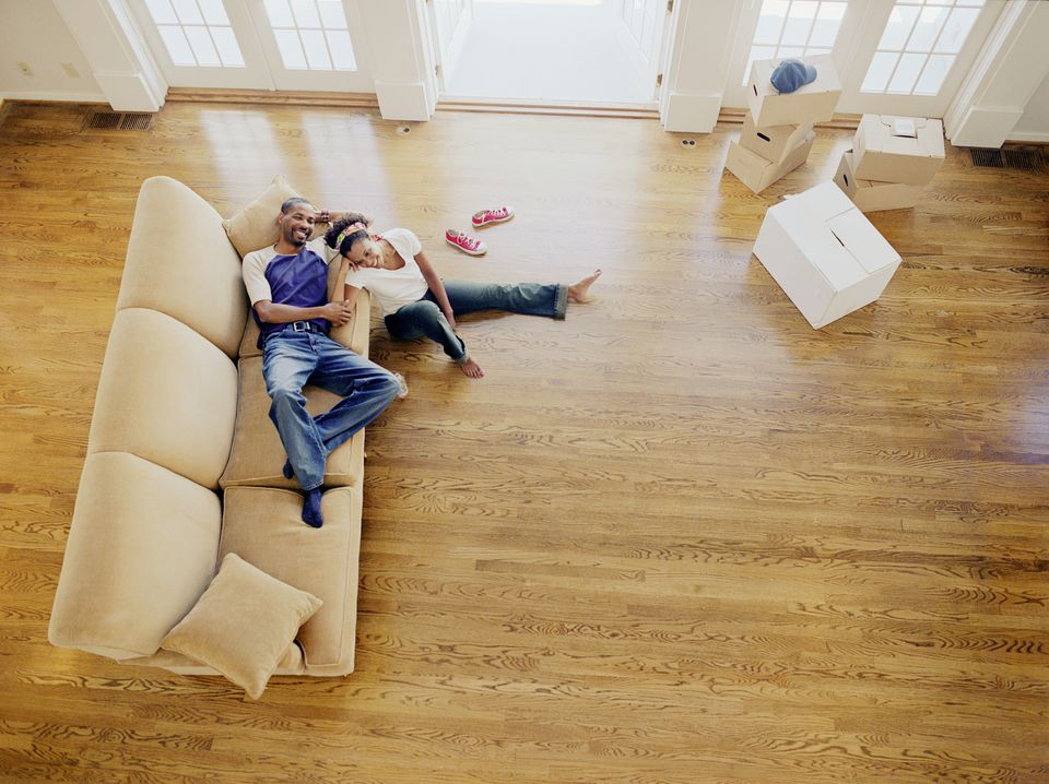 Couple resting on sofa in new home, elevated view
