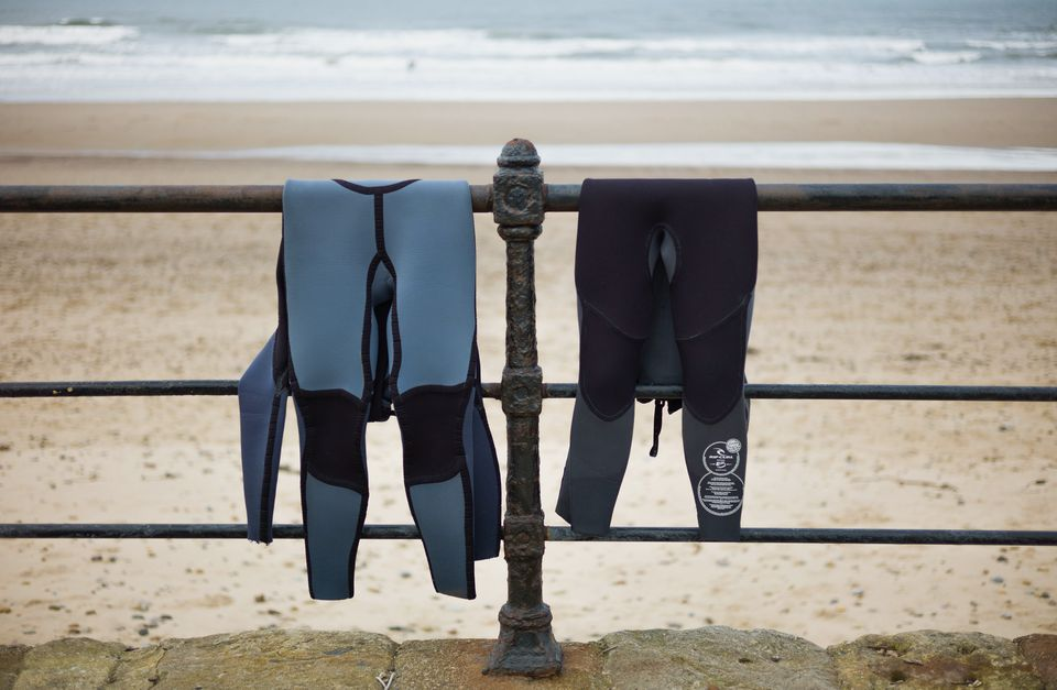 A blue and black wet suit hanging over a railing near a beach.