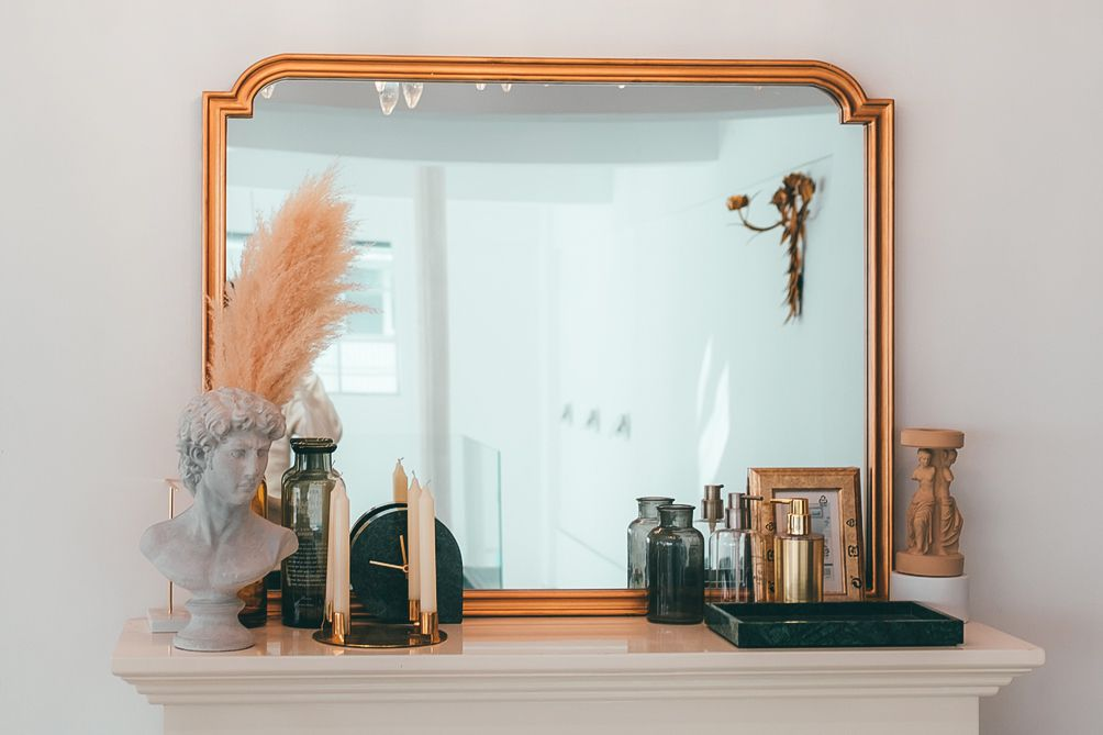 large gilded statement mirror on a mantel
