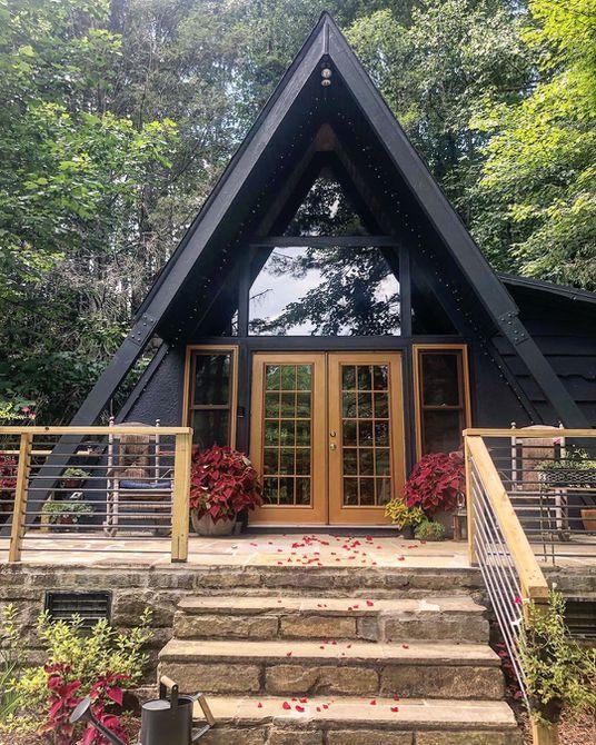 una casa de marco negra con un porche