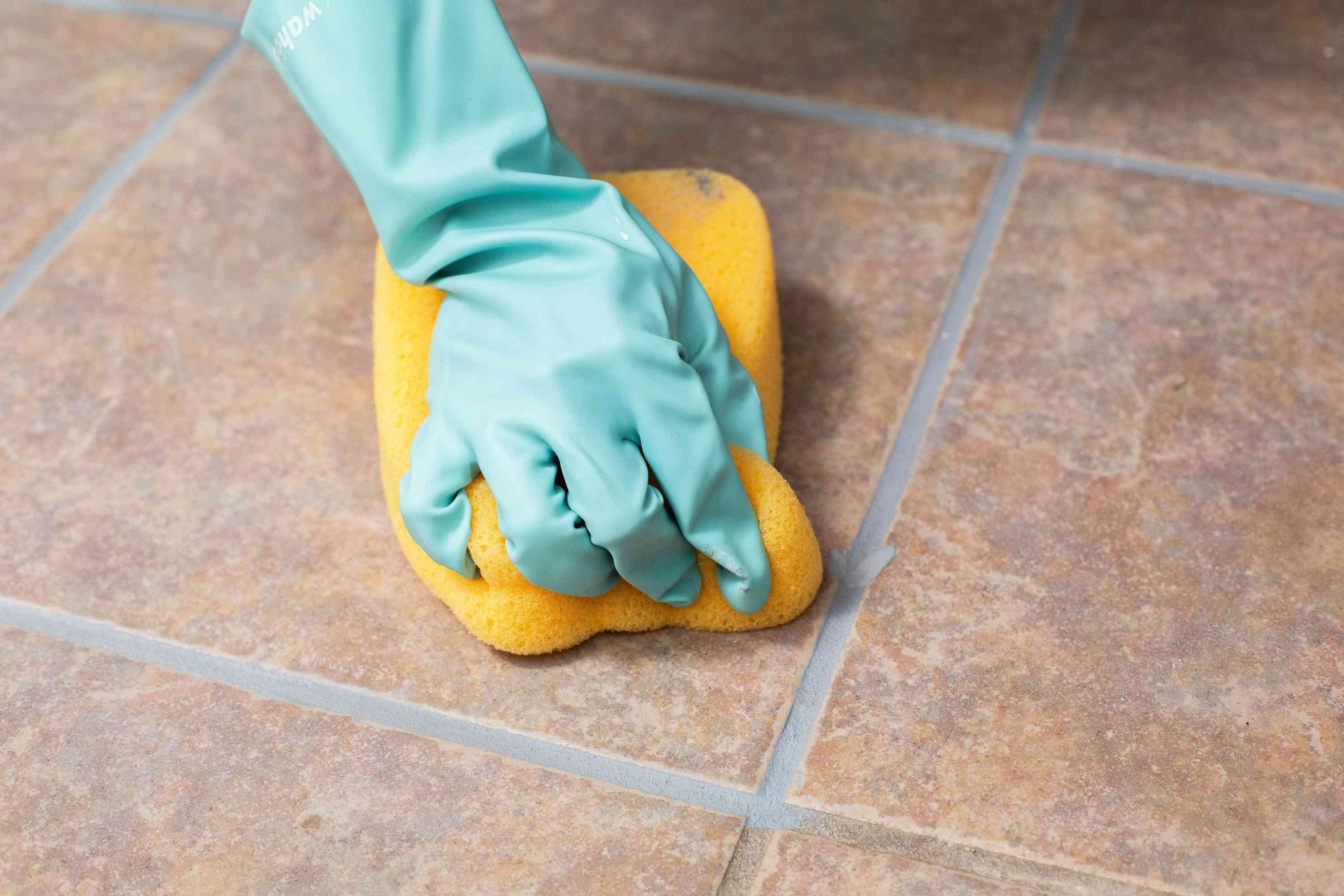 Excess colorant cleaned with yellow nylon-faced sponge on tile floor