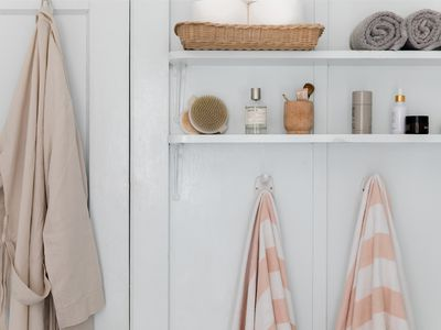 Hooks on white wall holding up a tan robe and white and pink fabrics below shelving