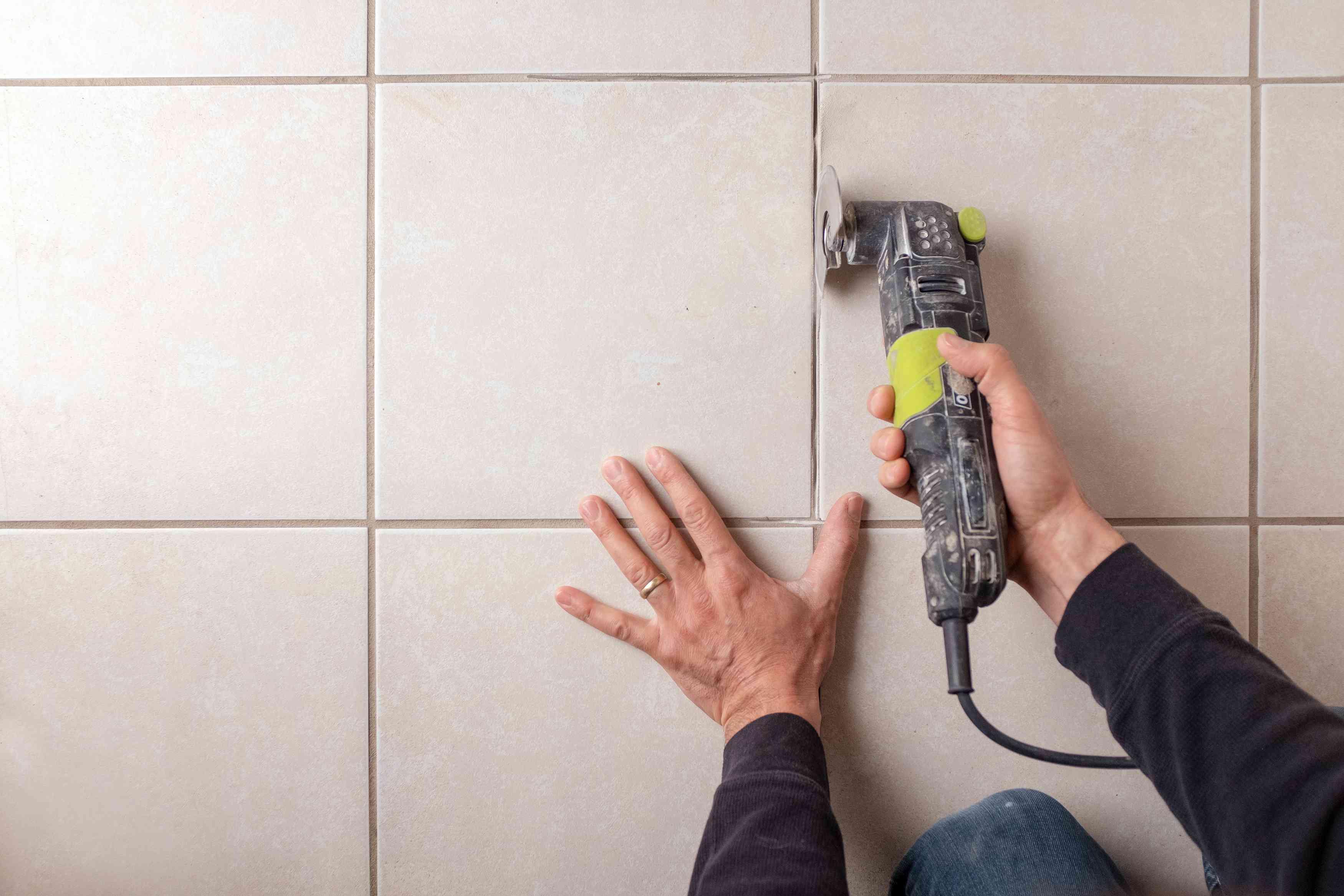 Man using oscillating tool on tile grout
