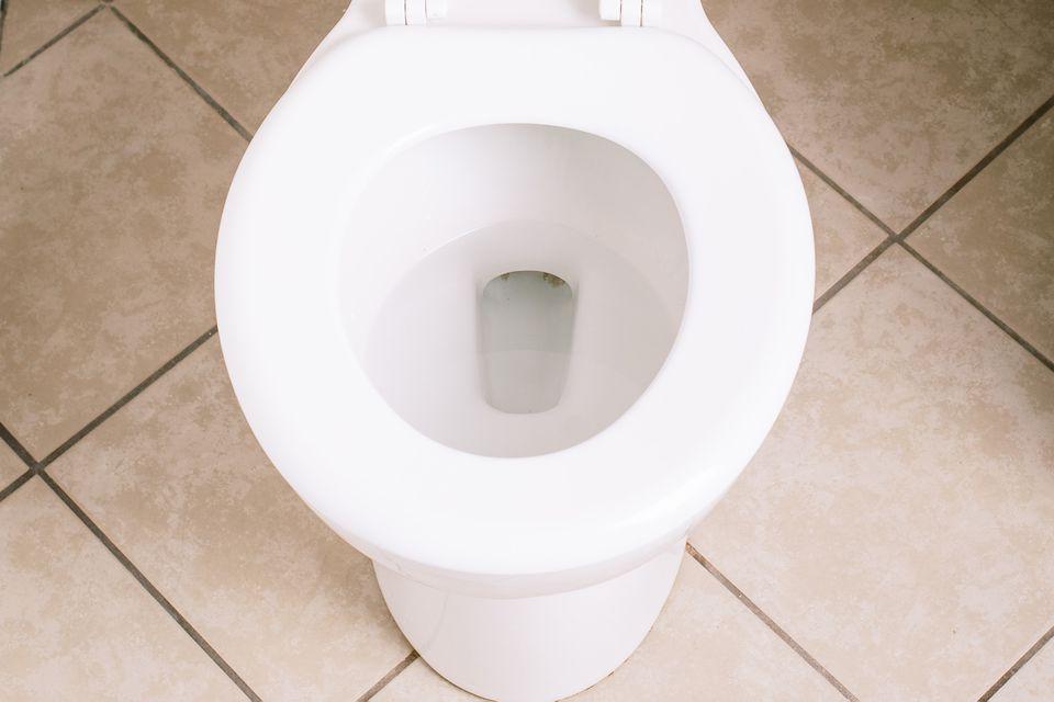 White ceramic toilet surrounded by tan tiles closeup