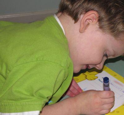 Una foto de un niño escribiendo una nota de agradecimiento