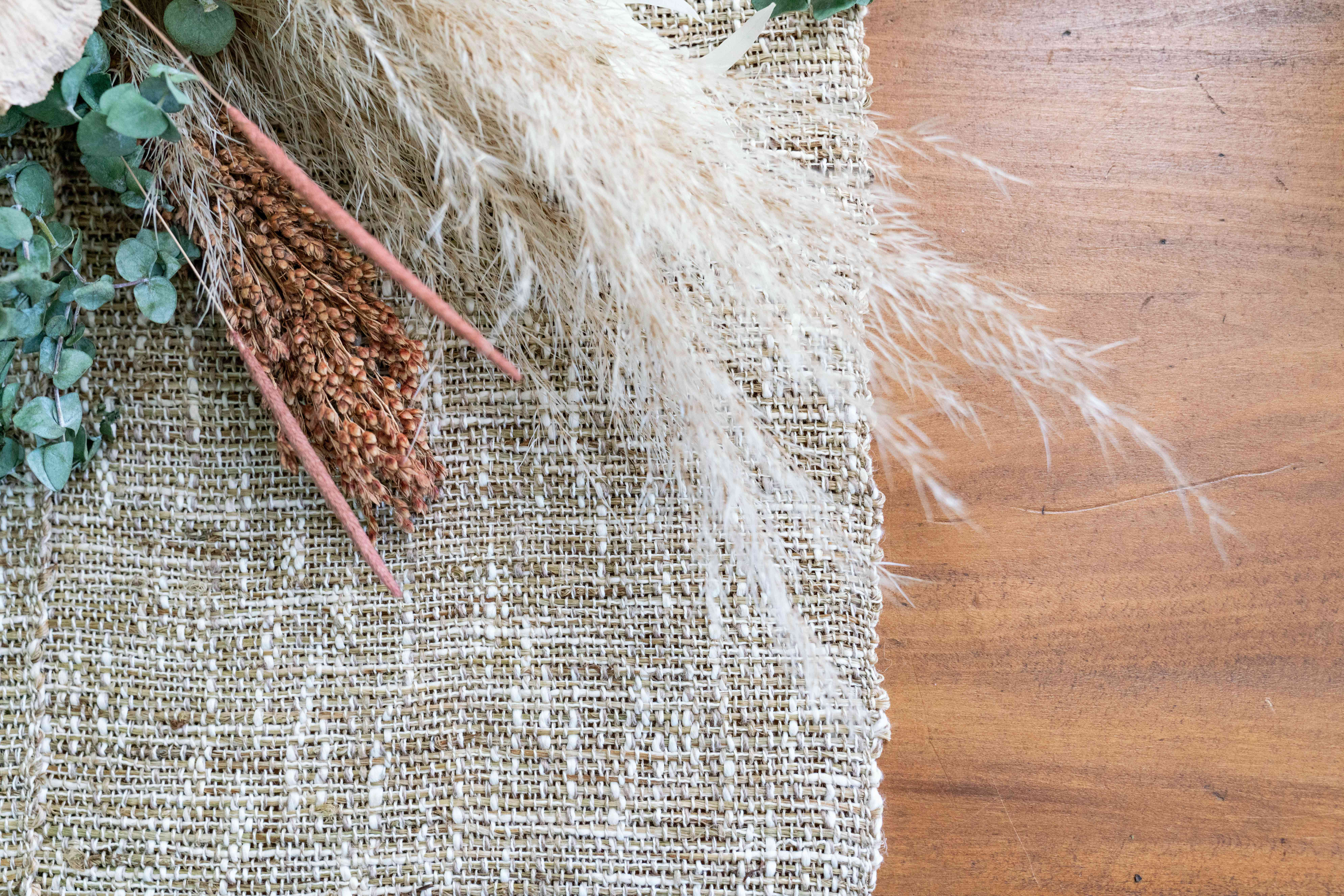 Jute fabric laid on wooden surface with assortment of dried florals on top