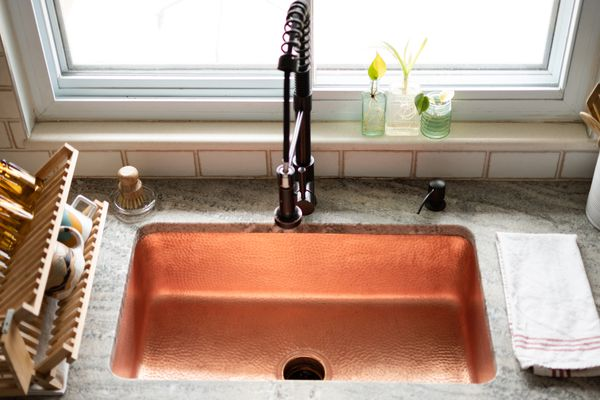 Kitchen sink with copper lining in front of window