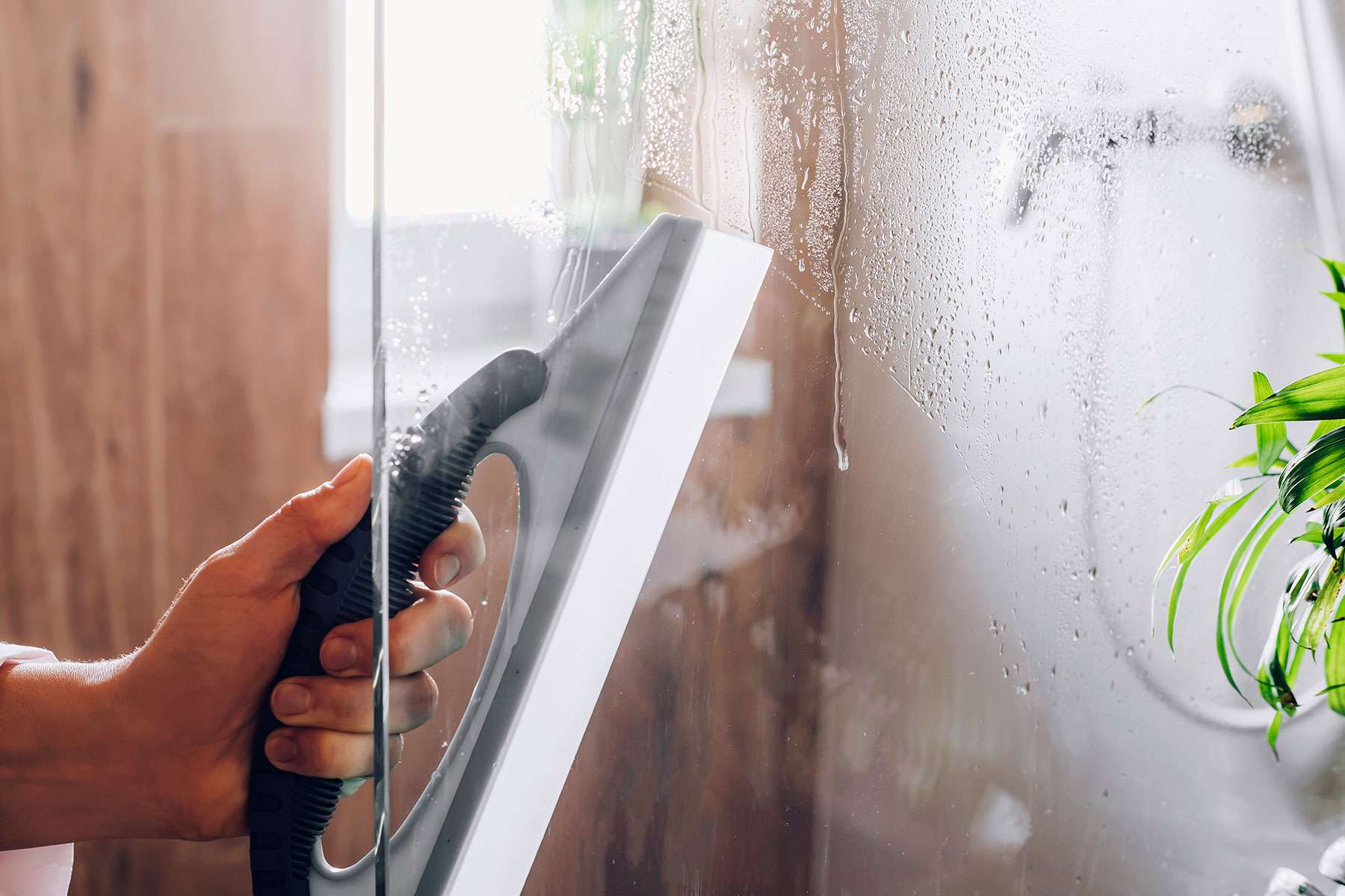Squeegee passing over glass shower door to remove water drops