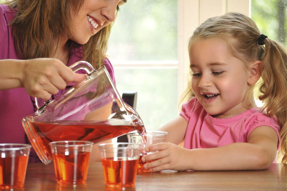 A woman pouring a girl a glass of Kool Aid