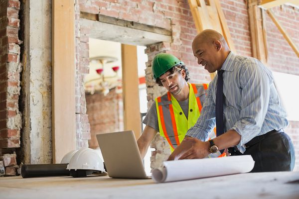 Male architect and tradesman discussing plan on laptop at construction site