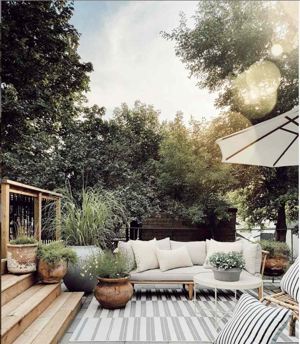 patio with white and wood patio furniture, oversized umbrella