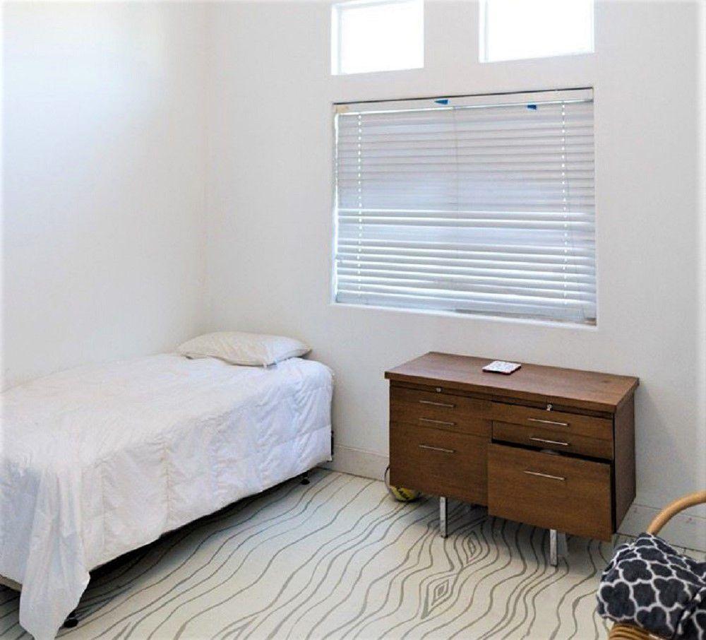 Revestimiento del dormitorio del niño con habitación blanca y cómoda pequeña