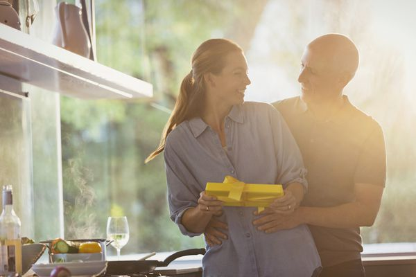 Smiling husband surprising wife with gift in sunny kitchen