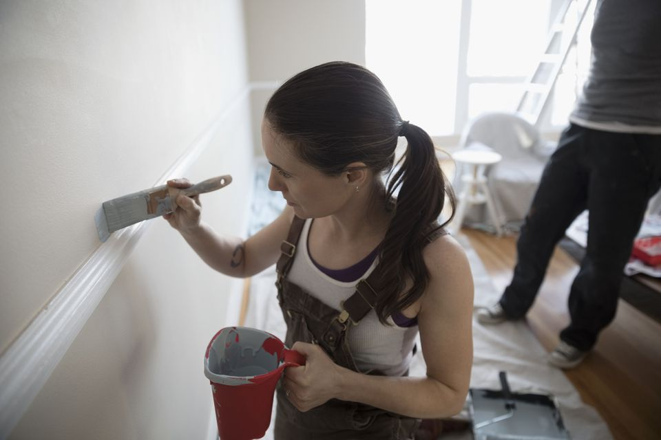Woman cutting in paint on a wall
