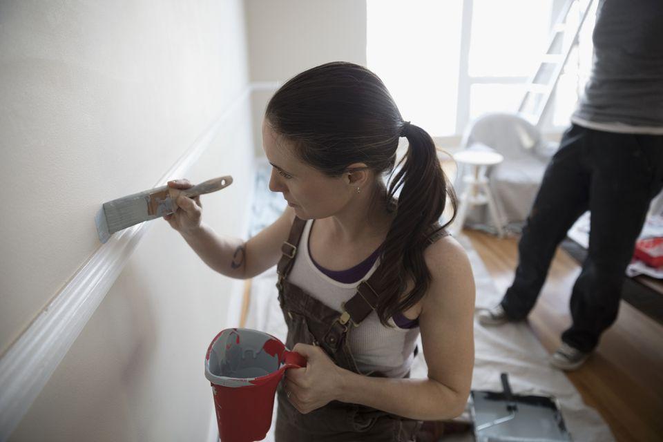 Mujer cortando pintura en una pared