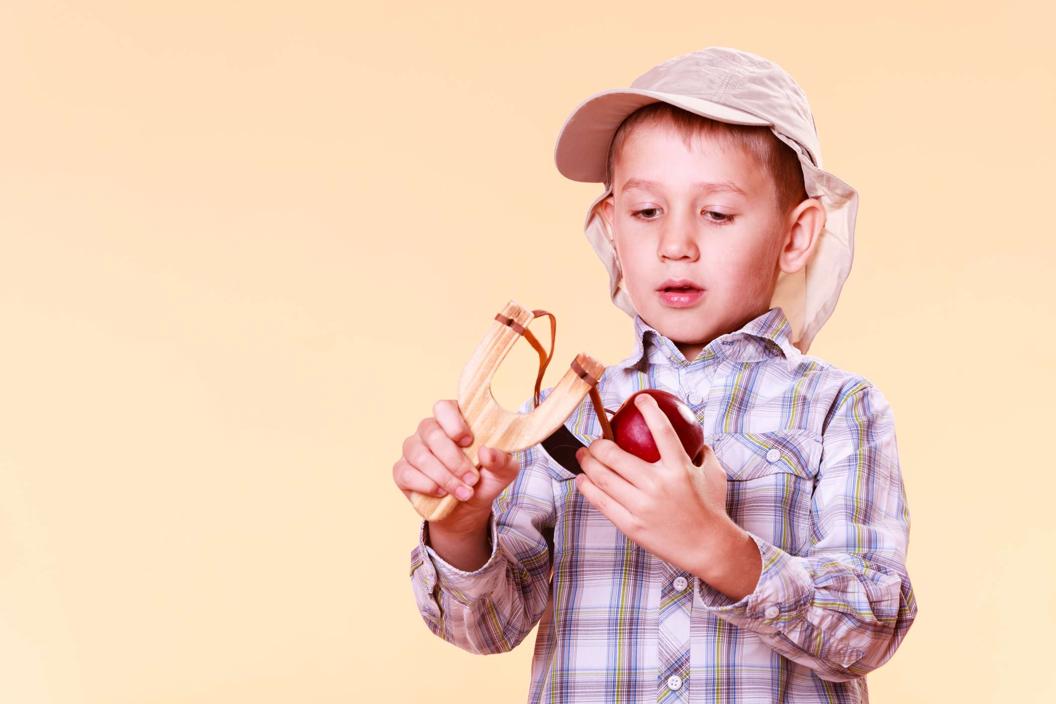 child putting an apple into a sling shot