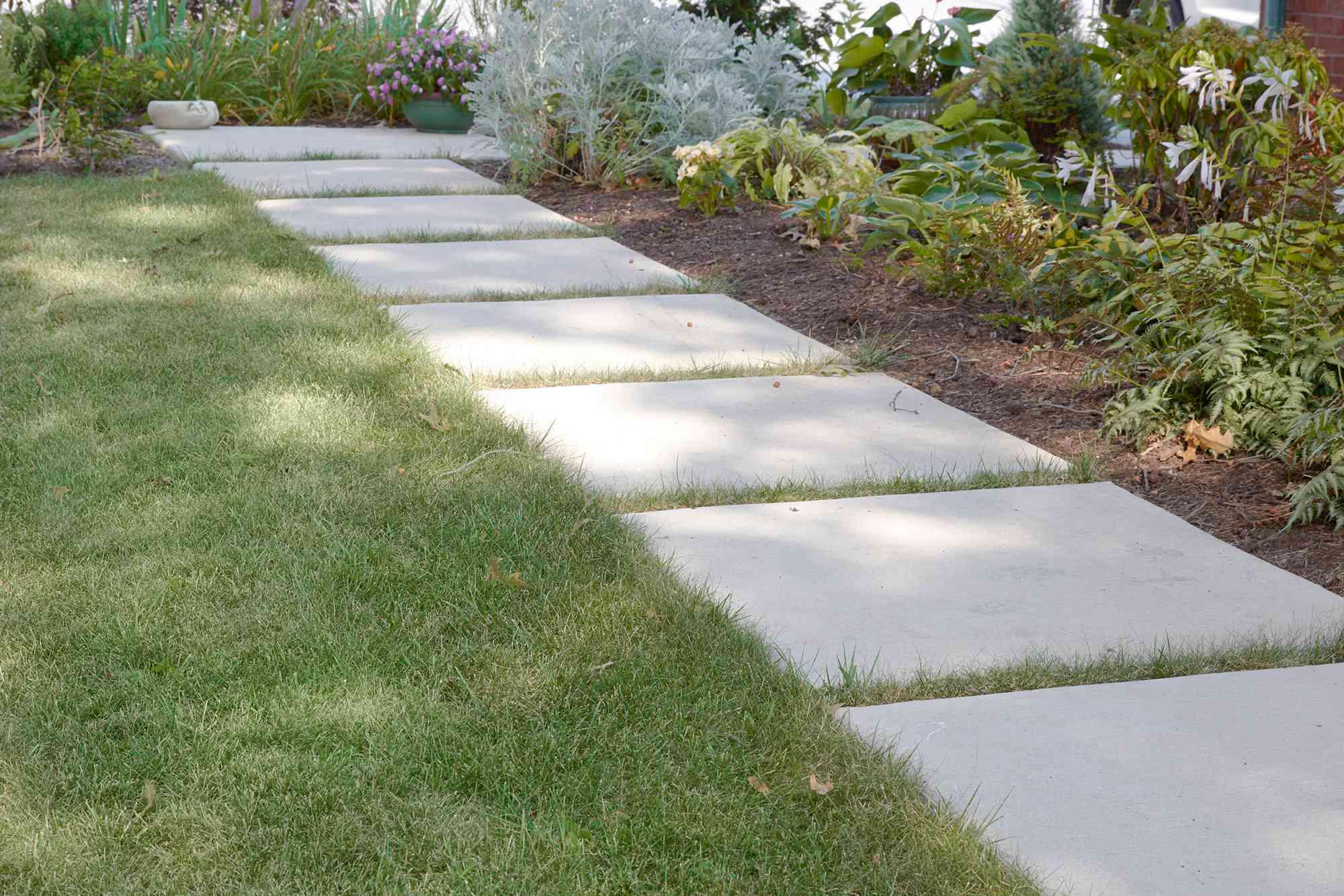 White stone walkway next to grass lawn checked for slope causing wet basement