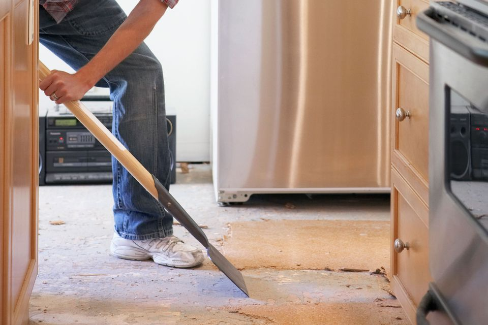 Man removing floor in kitchen
