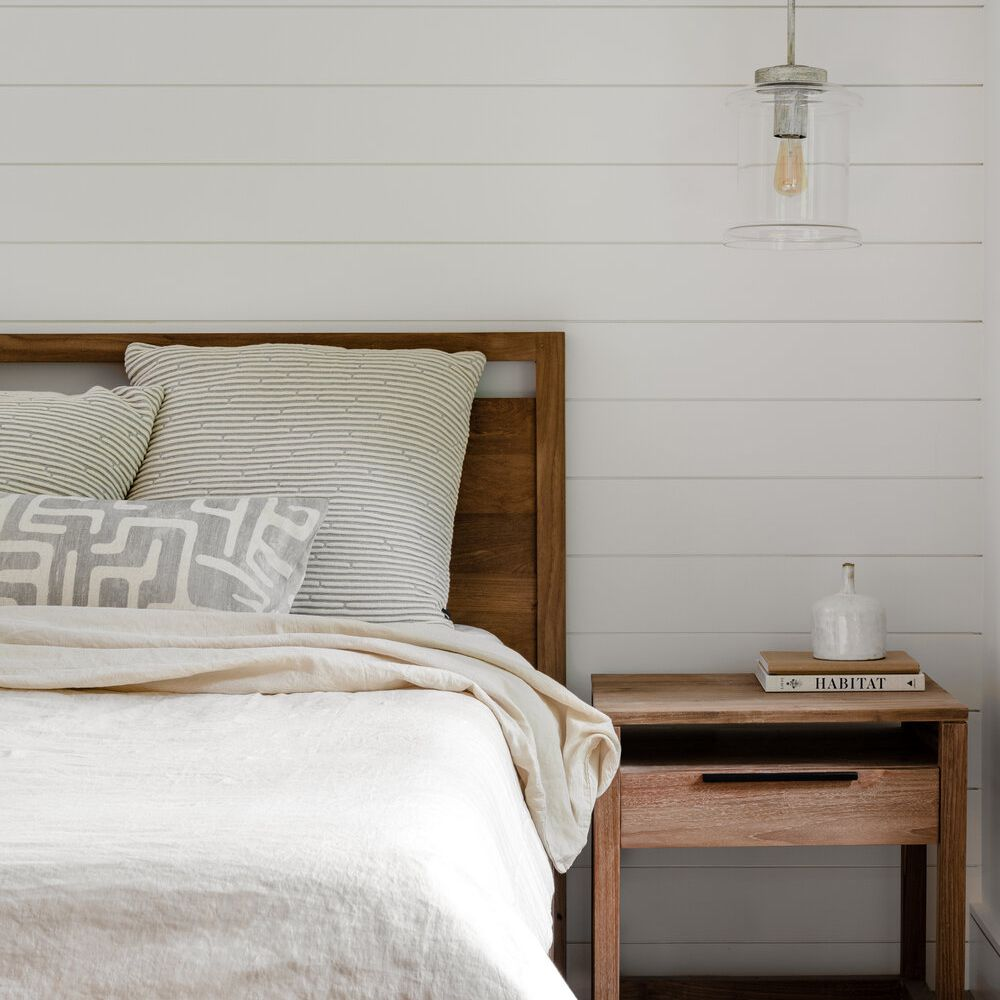 neutral bedroom with white shiplap walls and wooden bed frame/bedside table