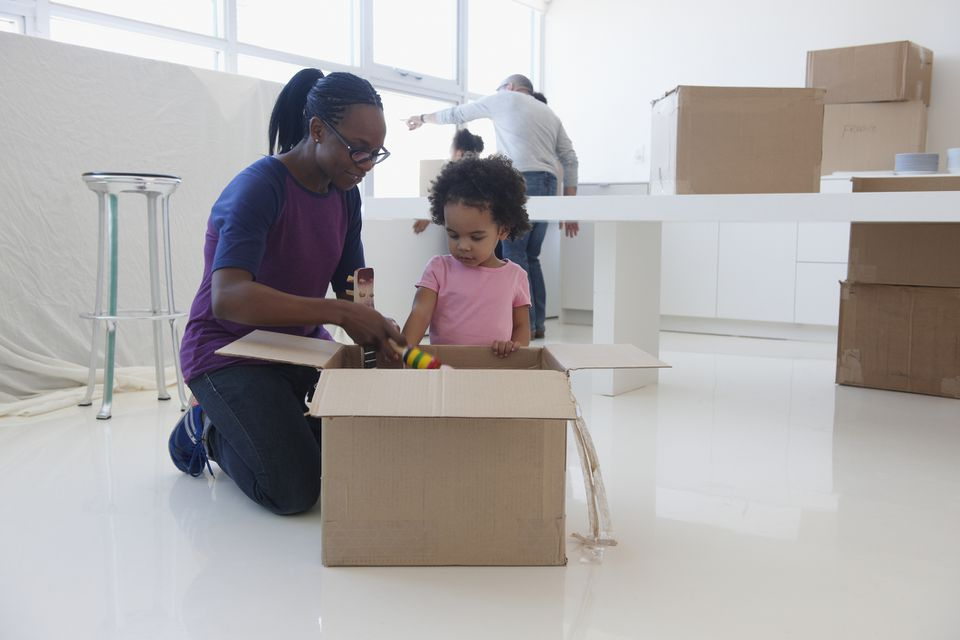 Mother and daughter packing box on moving day