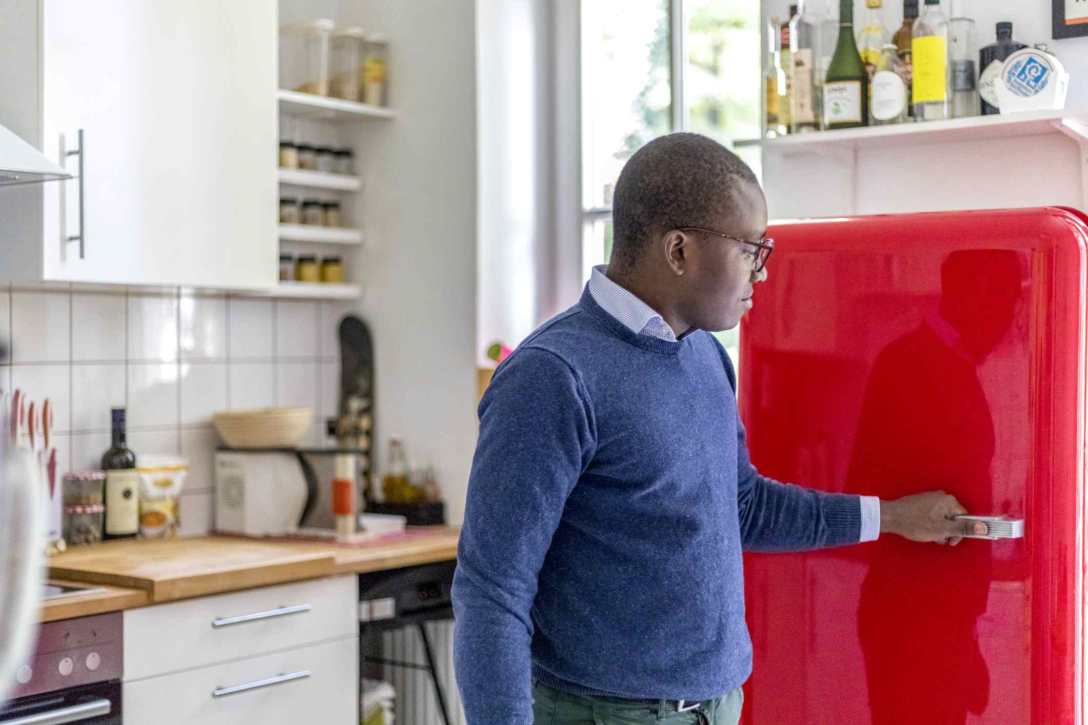 Man opening a red refrigerator.