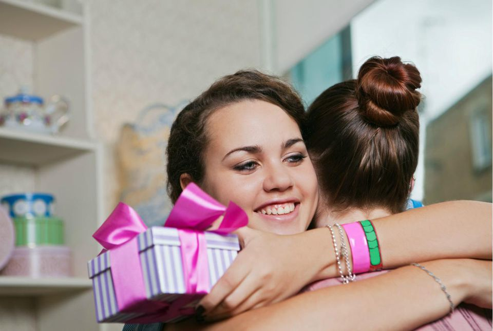 Young women holding gift and embracing