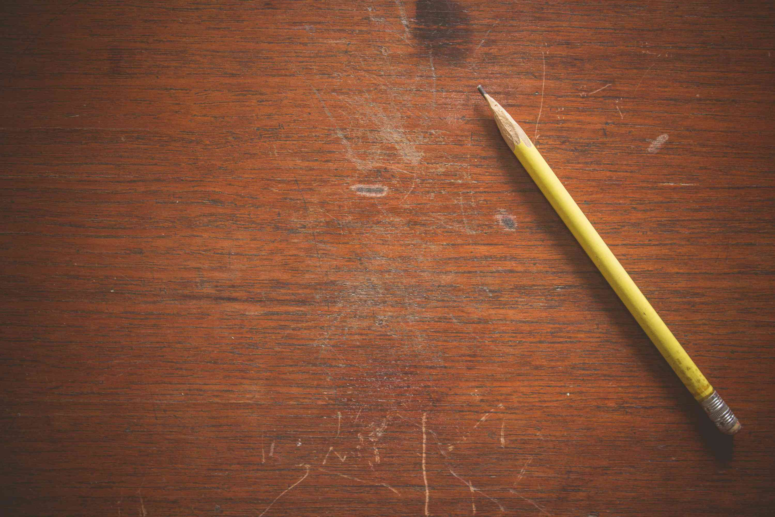 Yellow pencil on scratched wood desk