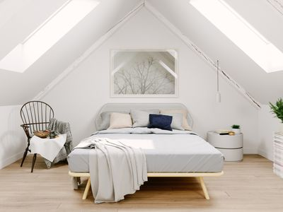 Renovated attic bedroom with white walls and two big skylights.
