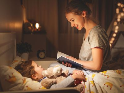 Woman reading to child by nightlights in bedroom