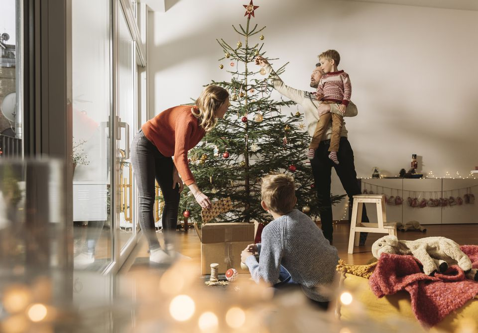 Family of four decorating a Christmas tree