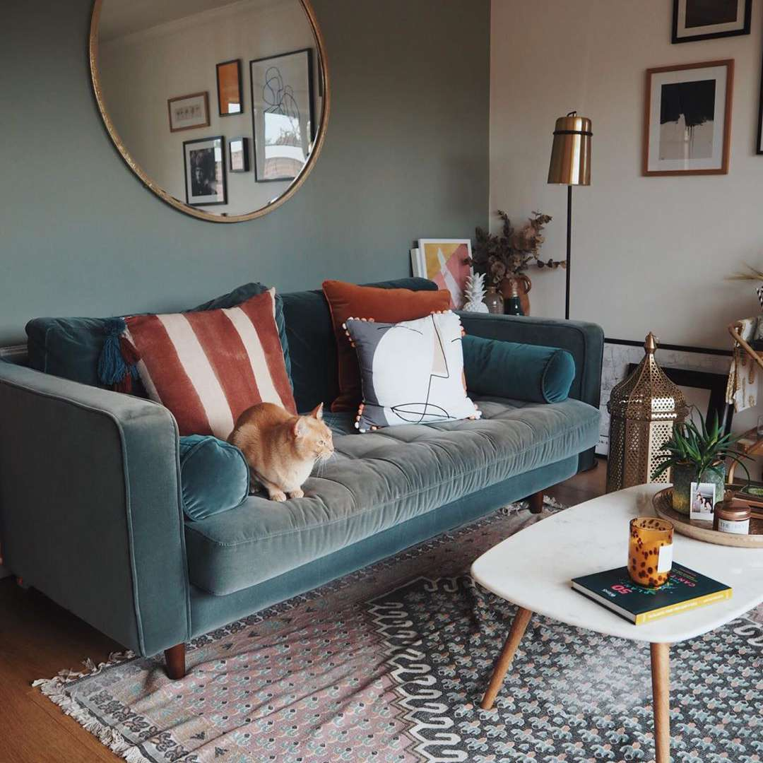 Living room with blue couch and orange pillows